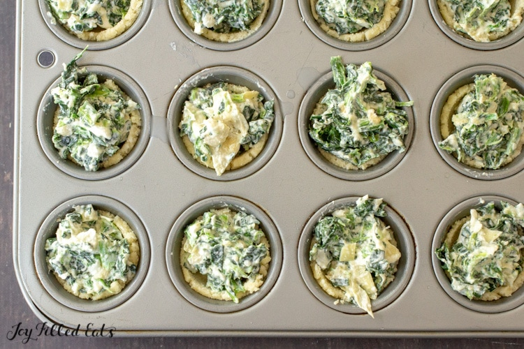 a mini muffin tin with dough cups filled with keto spinach artichoke dip