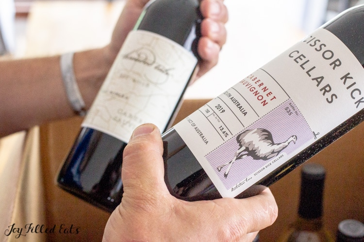 hands holding 2 bottles of wine