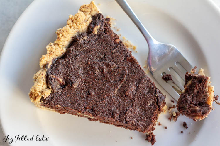 a piece of keto chocolate tart on a plate with a bite on a fork