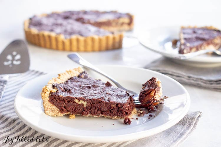 a slice of keto chocolate brownie tart on a plate with a bite on a fork
