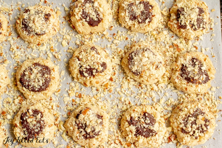 almond crunch chocolate thumbprint cookies lined on a cookie sheet and covered in chopped almonds