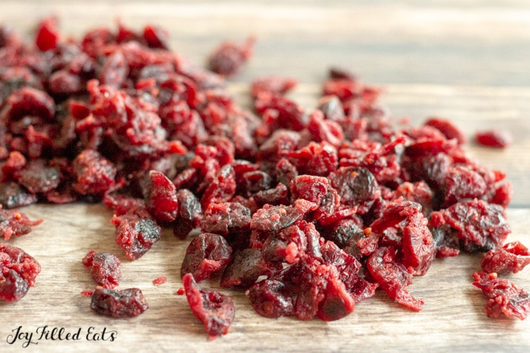 dried cranberries spread out on a wood surface