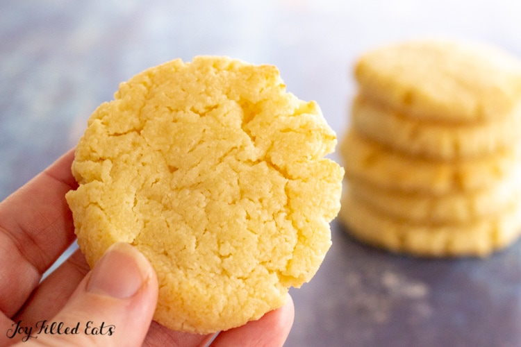 a hand holding up one of the keto butter cookies