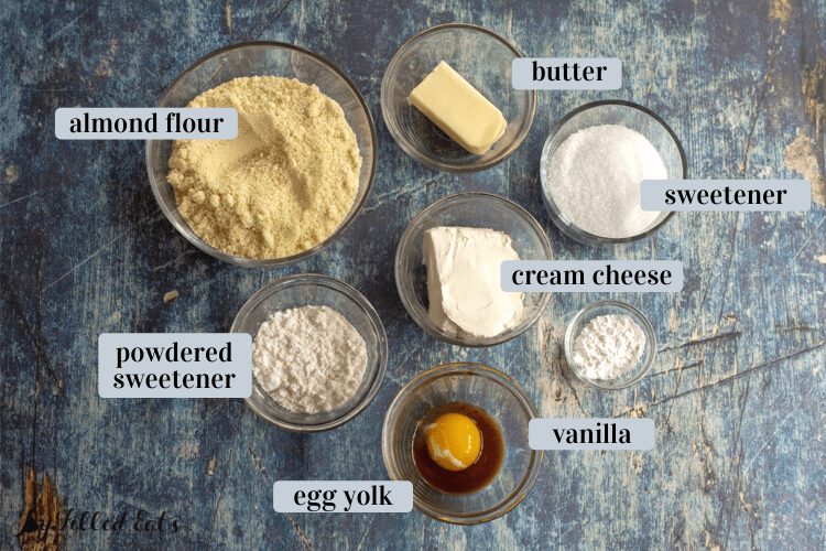 ingredients in small bowls including almond flour, cream cheese, sweetener, and butter