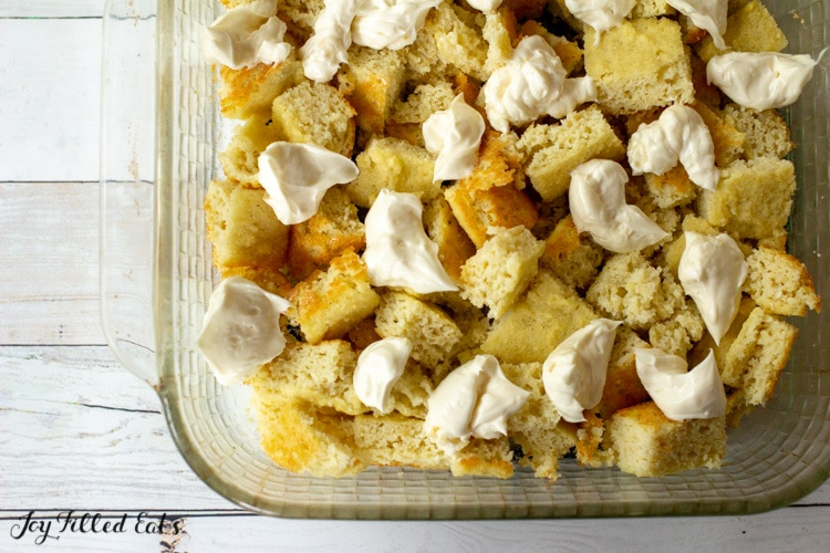 assembling the keto french toast casserole with cubed of bread and dollops of sweetened cream cheese