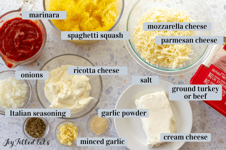 ingredients in small bowls including squash, cheeses, and spices