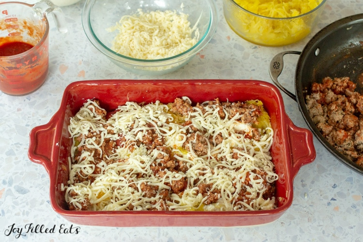 a casserole dish with squash, meat, cheese