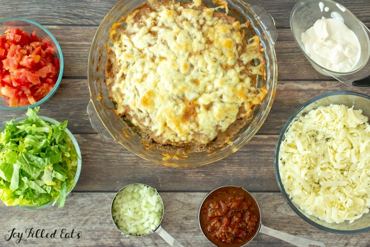 the baked keto taco pie with small bowls of toppings around it