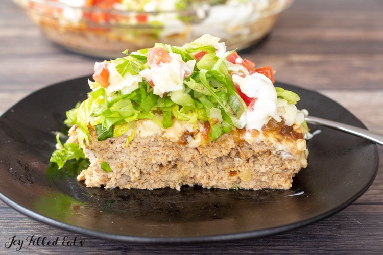 a slice of the low carb taco pie on a black plate