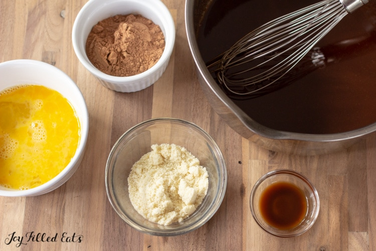 chocolate in a saucepan with small bowls of vanilla, almond flour, cocoa powder, and eggs
