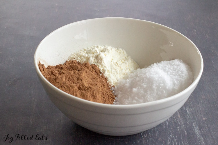 a white bowl with cocoa powder, heavy cream powder, and sweetener