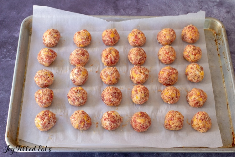 a baking sheet lined with parchment with 30 keto sausage balls