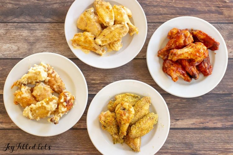 four plates of chicken wings with different toppings