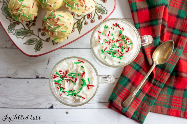 overhead shot of 2 glass mugs and a plate with hot cocoa bombs