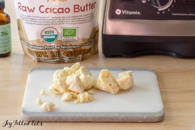Raw cacao butter scattered on a small cutting board set in front of ingredients packages