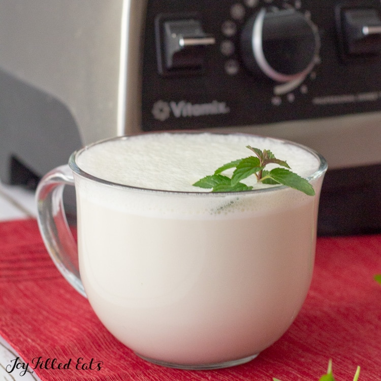 glass mug of peppermint white hot chocolate with a mint leaf garnish next to a Vitamix blender