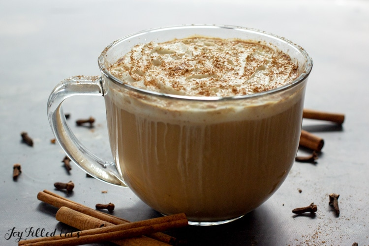 glass mug with keto chai tea latte topped with whipped cream