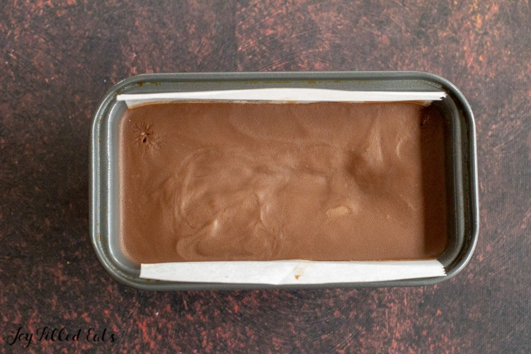 keto chocolate fudge in small loaf pan lined with parchment paper after chilling