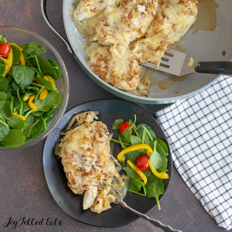 overhead shot with a plate with chicken and salad, a skillet of keto french onion soup chicken, and a large salad bowl