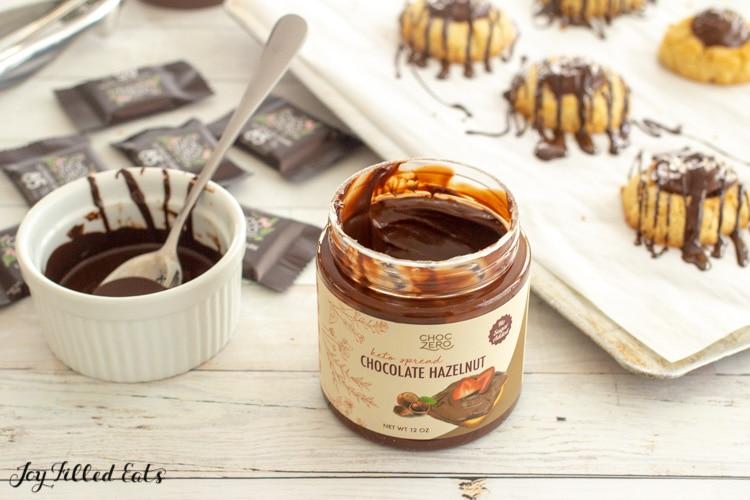 a jar of choczero chocolate hazelnut spread next to a small bowl of melted dark chocolate