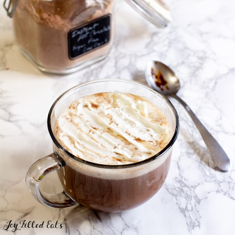 sugar free hot chocolate mix in a jar next to a mug of hot cocoa