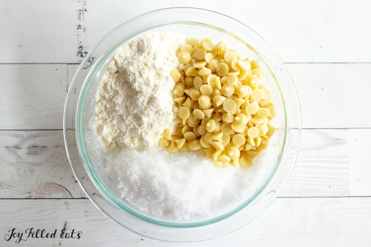 glass bowl with white chips, sweetener, & heavy cream powder