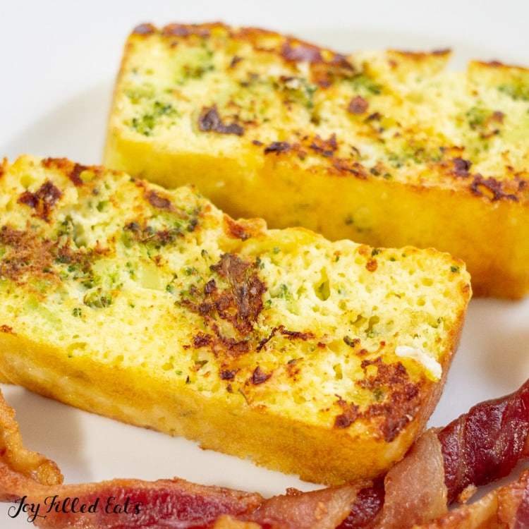 two slices of broccoli and cheddar loaf on a white plate with strips of bacon