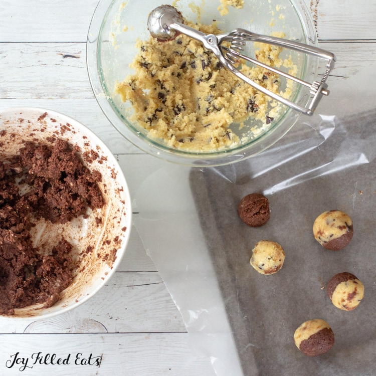 one bowl of edible cookie dough with a small cookie scoop and one bowl of brownie dough