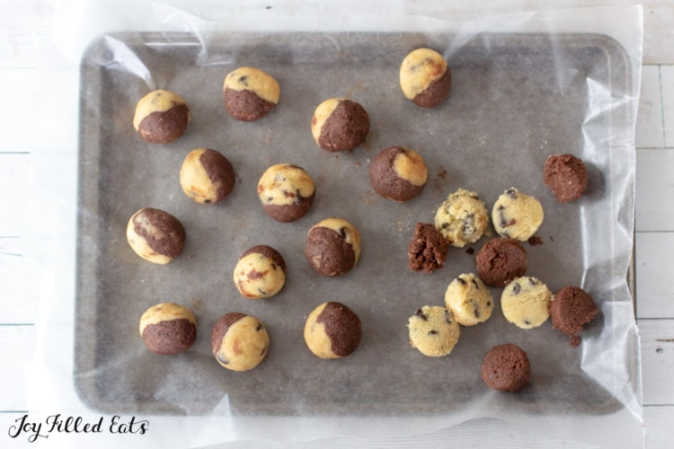 balls of half edible cookie dough and half brownie dough on parchment paper