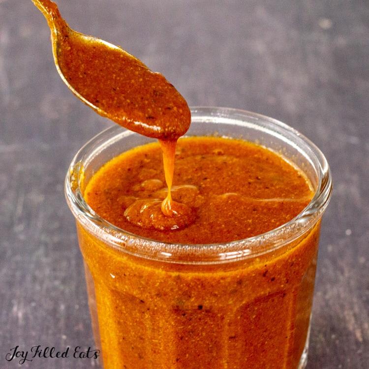spoon showing keto enchilada sauce in jar