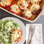 overhead shot of the chicken parm stuffed peppers on a plate with a salad and in the casserole dish