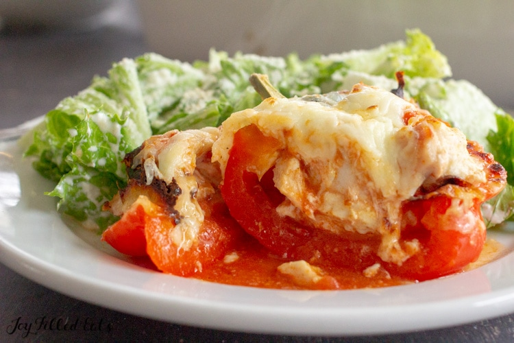chicken parm stuffed pepper cut in half on a plate with a salad
