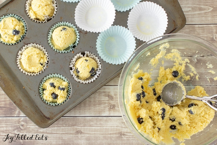 a muffin pan with paper liners, a bowl with batter, and a large cookie scoop