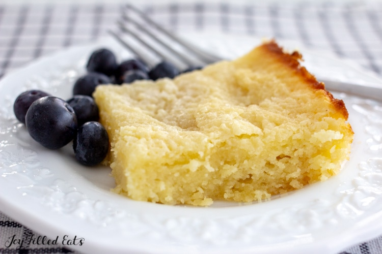 piece of keto butter cake on a small white plate with a fork and blueberries