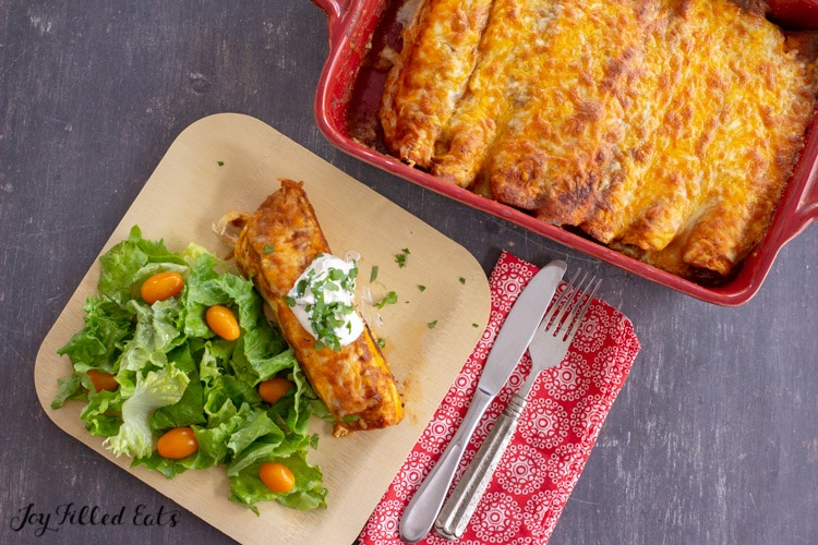 overhead shot of the keto chicken enchiladas in the baking dish and served on a plate with a salad