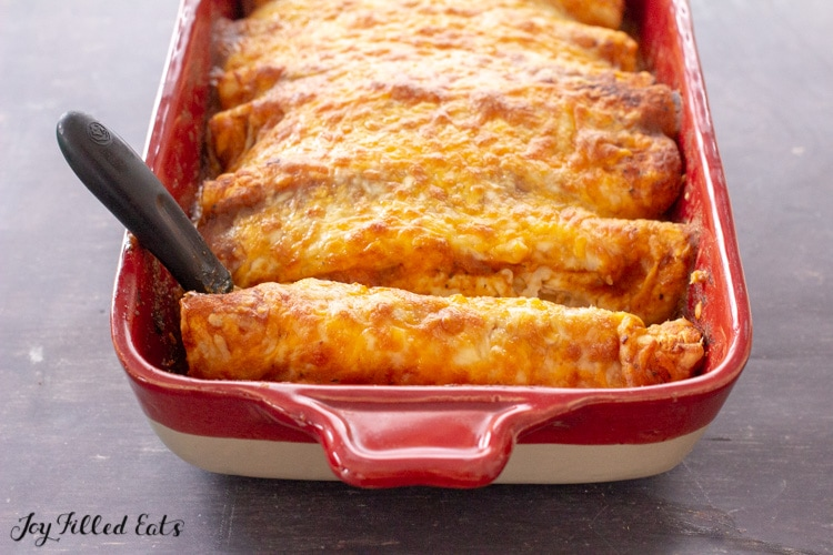 keto chicken enchiladas baked in a casserole dish with a serving spatula