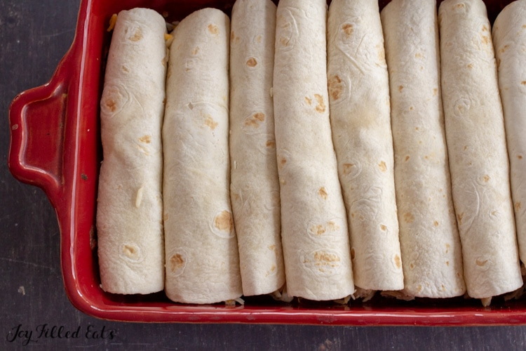 tortillas rolled around filling in a casserole dish