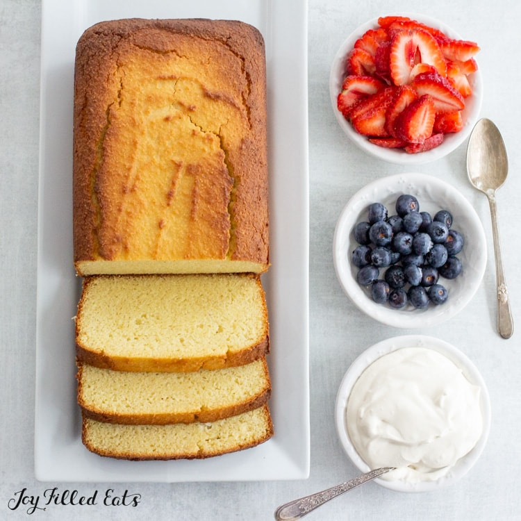 keto pound cake on a serving platter with small bowls of whipped cream and berries