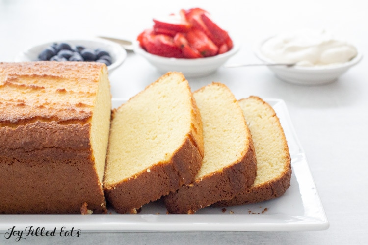 slices of keto pound cake on a serving platter with small bowls of whipped cream and berries