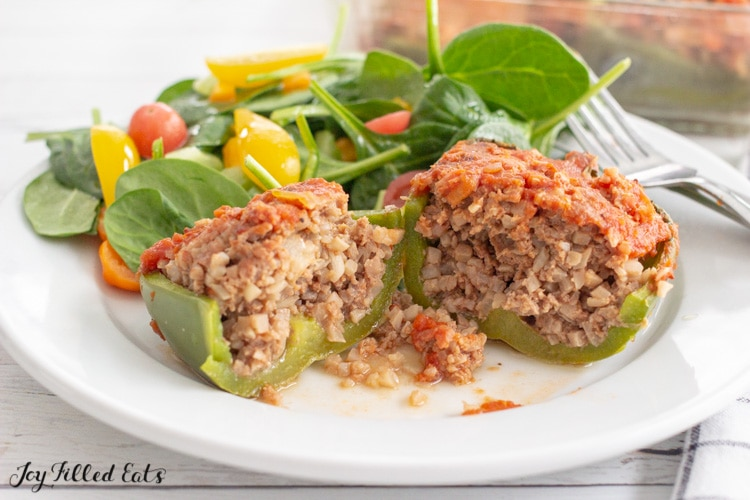 one of the whole30 stuffed peppers cut in half on a plate