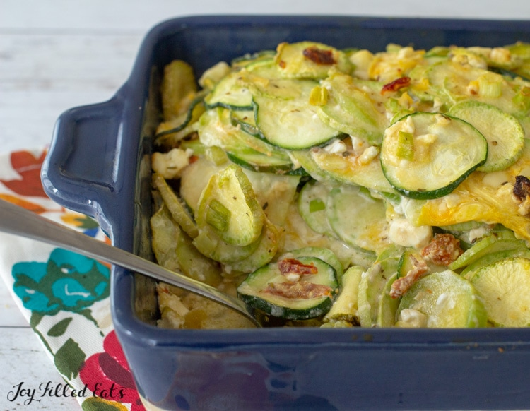 zucchini au gratin in a serving dish with a spoon