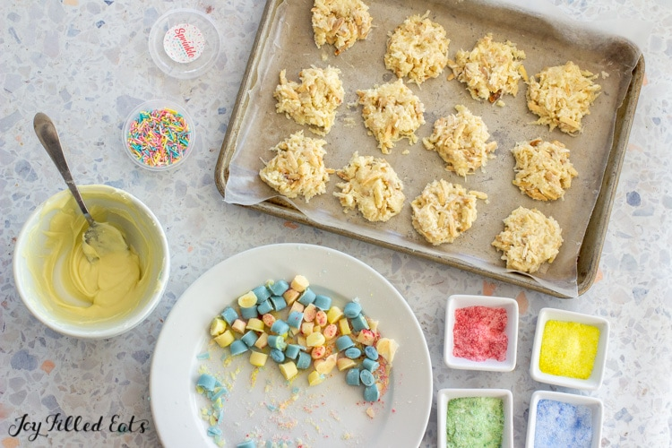 tray of no bake cookies with bowls of melted chocolate and colored sweetener