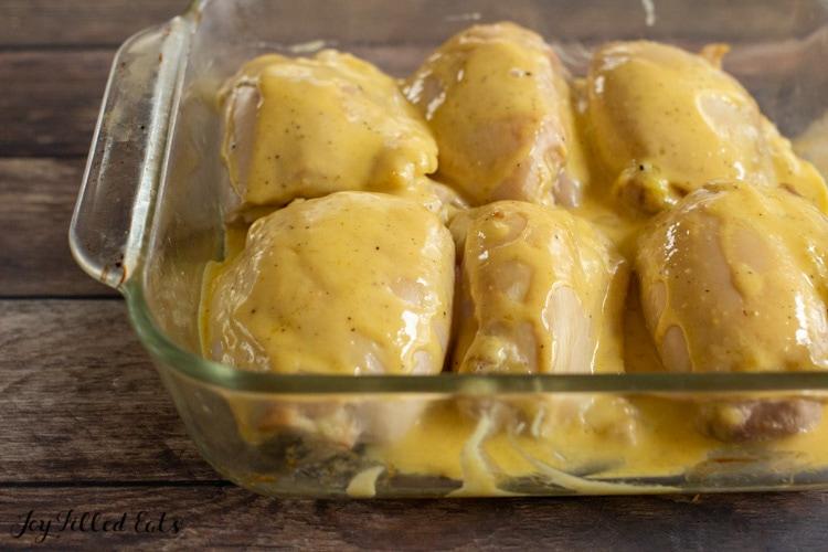 glass baking dish of buffalo chicken thighs