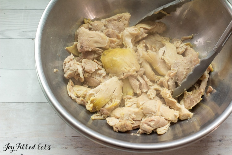 cooked chicken thighs in large bowl