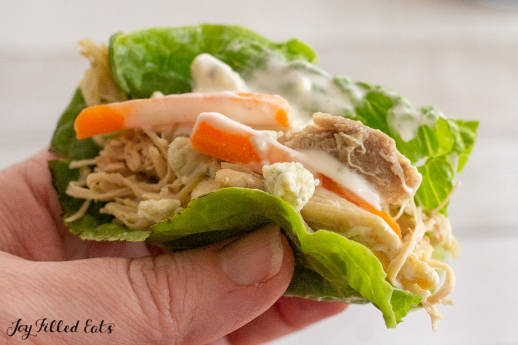 close up of a hand holding a lettuce wrap with keto pulled chicken