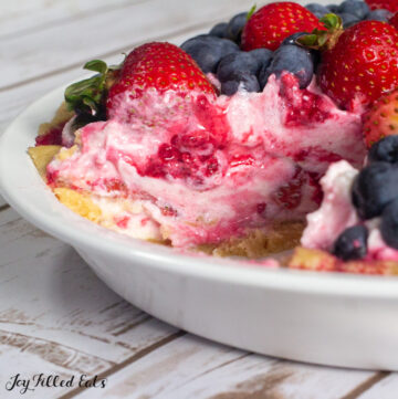 close up of cut cottage cheese cheesecake topped with berries