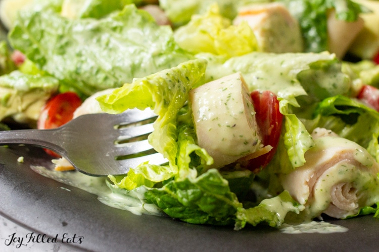 close up of salad in a black plate with fork
