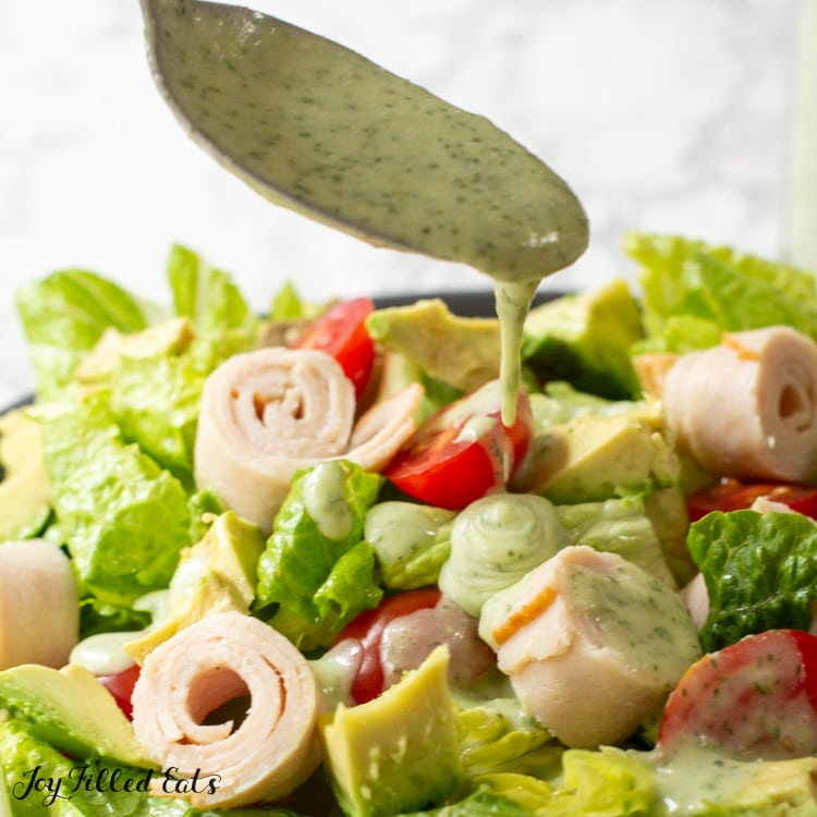 spoon drizzling dairy free ranch dressing onto salad close up
