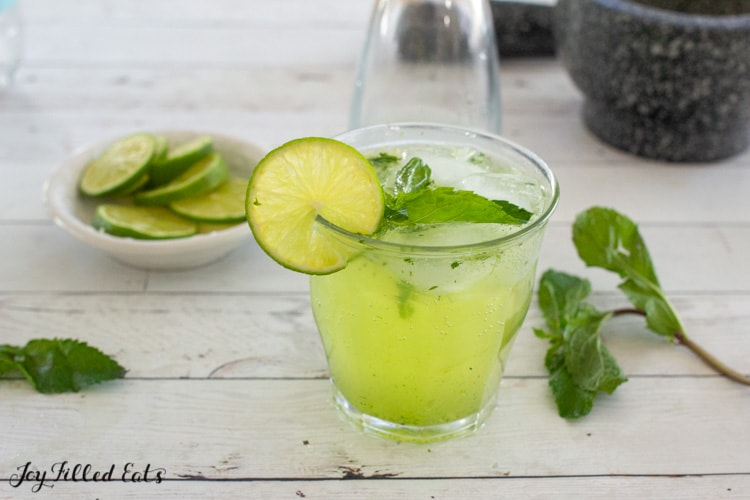 glass with mint and lime cocktail