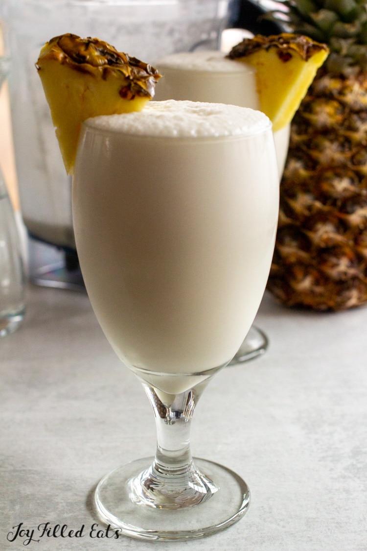 glass of keto pina colada with sliced pineapple garnish